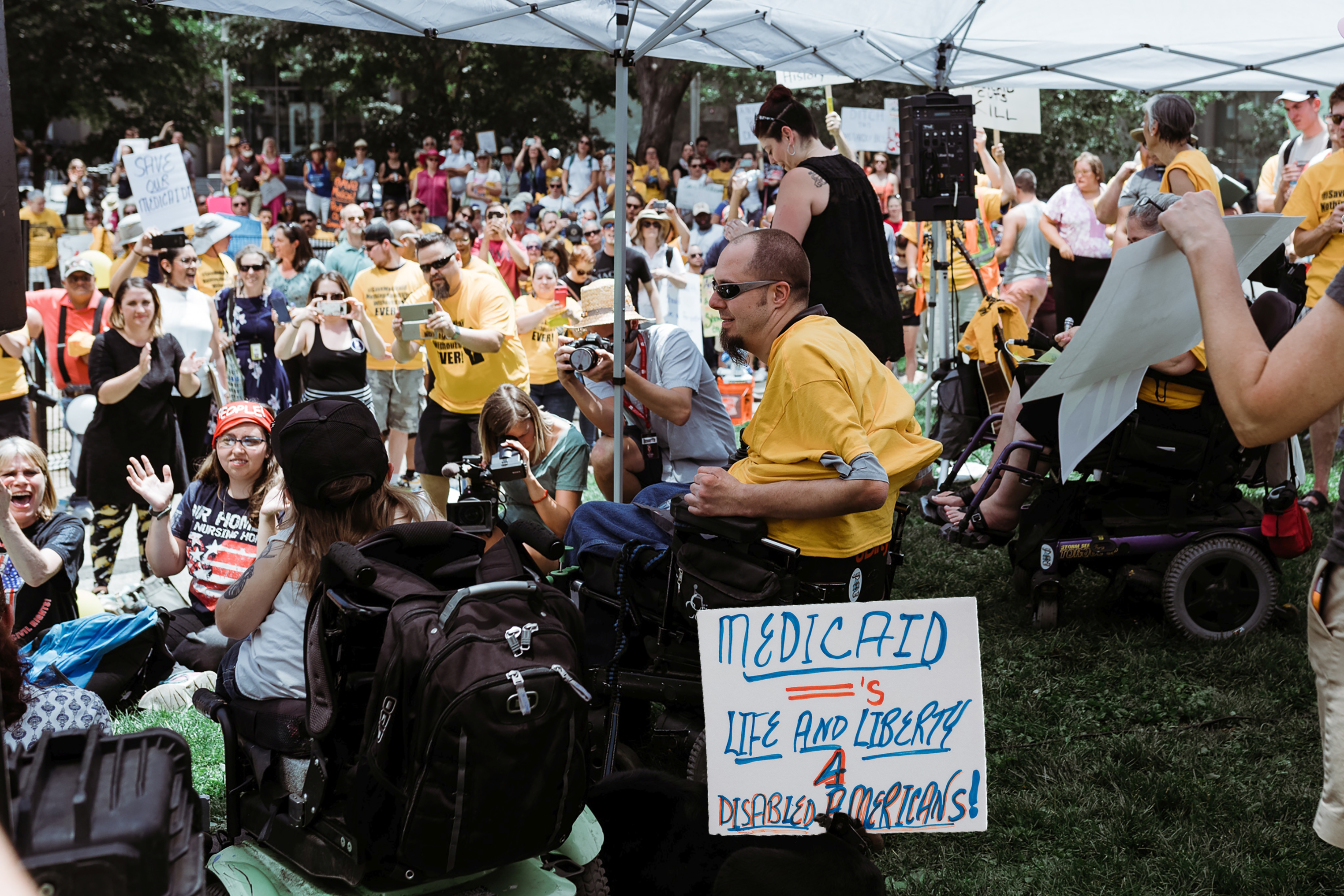 "Picture at the Save Medicaid Rally, Denver. ADAPT Members with a clear sign that reads: ""Medicaid Equals Life and Liberty for Disabled Americans"""