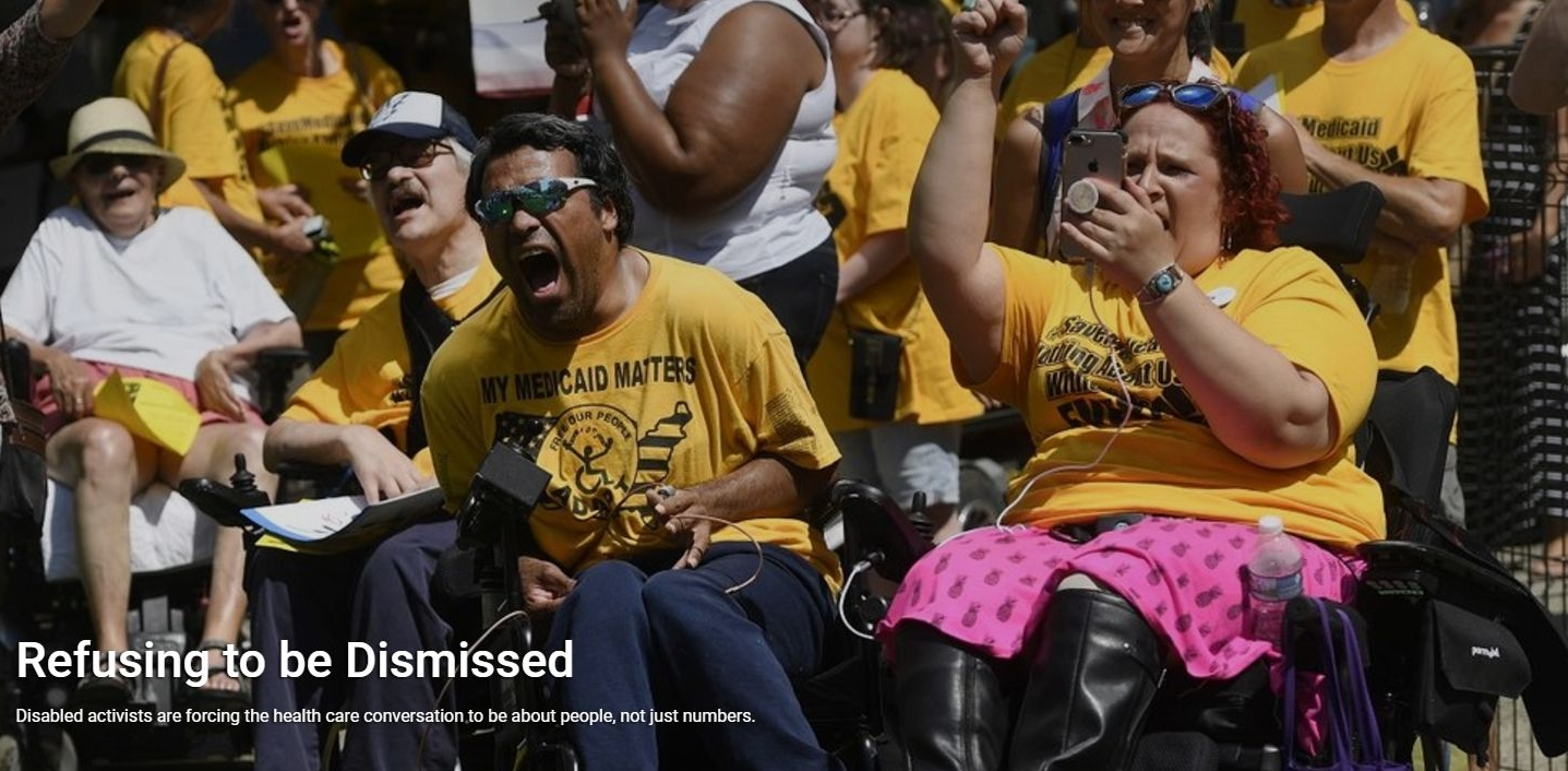 "Picture of two members of ADAPT, at the Save Medicaid Rally, with text that reads ""Refusing to be dismissed"""